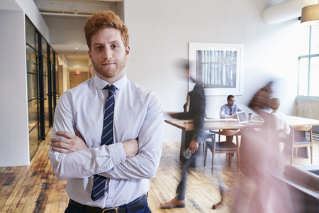 Portrait of young red haired man in a busy modern workplace