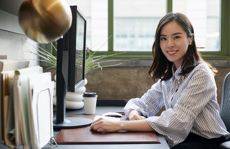 카메라에 미소를 사무실에서 컴퓨터에서 중국어 여자 스톡 콘텐츠