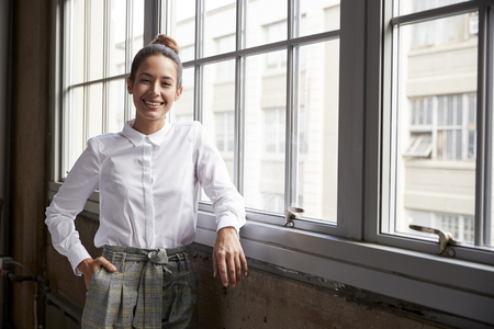 Young white businesswoman with hair bun smiling to camera Archivio Fotografico