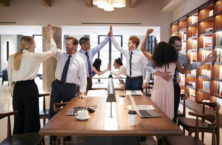 Six colleagues celebrating success in an open plan office Stock Photo