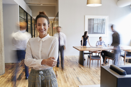 Portrait of young white woman in a busy modern workplace Stockfoto