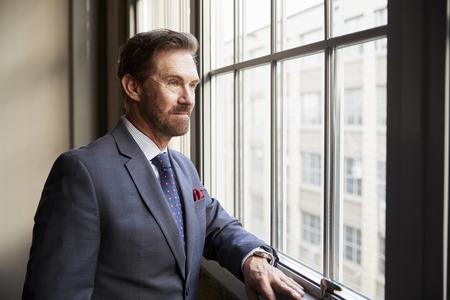 窓の外を見るシニア白人ビジネスマン