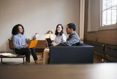 캐주얼 한 회의에서 랩톱을 사용하는 직장 동료들 미소 짓기 스톡 콘텐츠