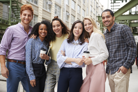 Six young adult coworkers standing outdoors, group portrait