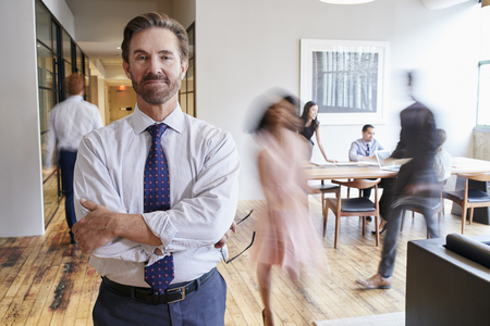 Portrait of middle aged white man in a busy modern workplace Stock Photo - 93472705