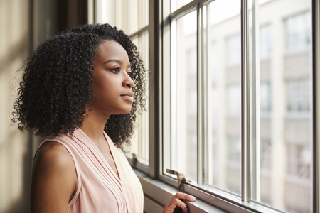 Young black businesswoman looking out of window Banco de Imagens