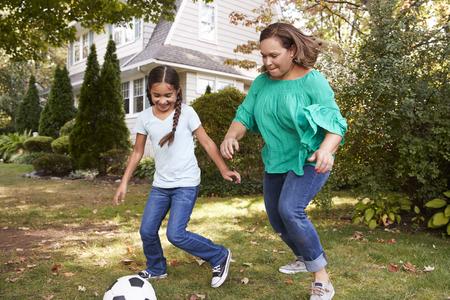 Grootmoeder die voetbal in tuin met kleindochter speelt