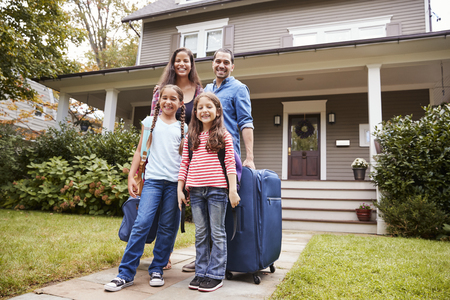 Portrait Of Family With Luggage Leaving House For Vacation Standard-Bild