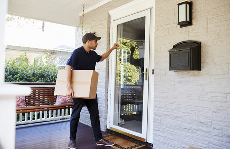 Courier Knocking On Door Of House To Deliver Package Banque d'images