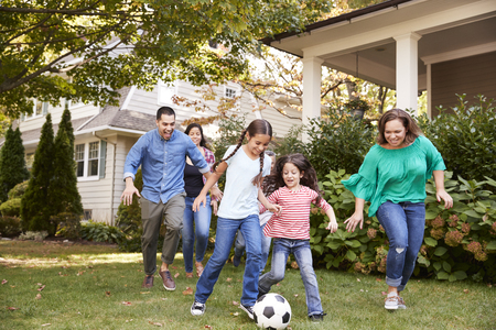 Multi Generation Family Playing Soccer In Garden Banco de Imagens
