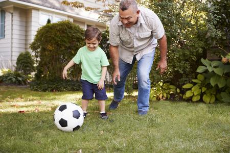 孫と庭でサッカーをするおじいちゃん 写真素材