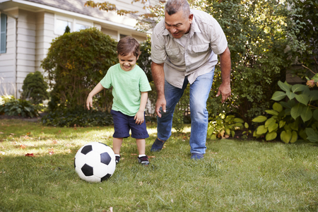 Grandfather Playing Soccer In Garden With Grandson Banco de Imagens - 94160060