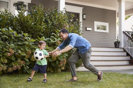Vader voetballen in tuin met zoon Stockfoto - 94362853