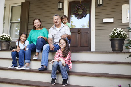 Grandparents With Grandchildren Sit On Steps Leading Up To Home