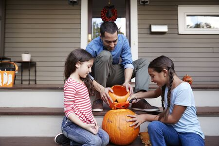 Father And Daughters Carving Halloween Pumpkin On House Steps Standard-Bild