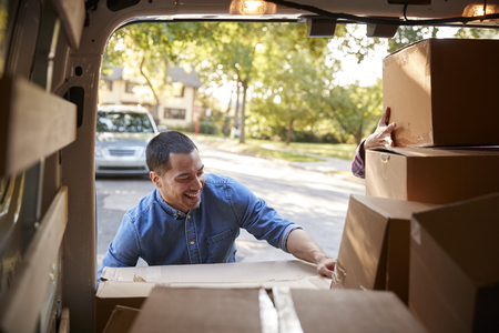 Couple Unloading Boxes From Van On Family Moving In Day