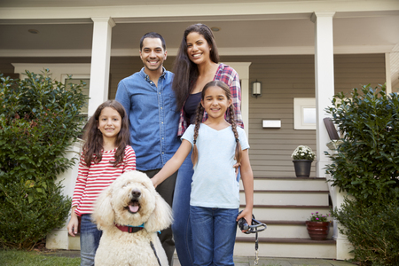 Portrait Of Family Standing in Front Of House With Pet Dog Standard-Bild