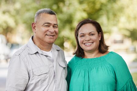 Portrait Of Smiling Senior Couple On Suburban Street