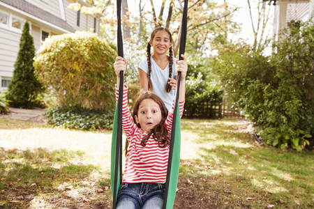 Two Sisters Having Fun On Garden Swing At Home Standard-Bild