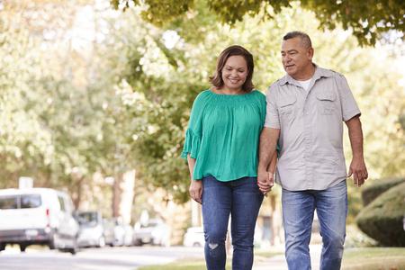 Senior Couple Walking Along Suburban Street Holding Hands Stockfoto