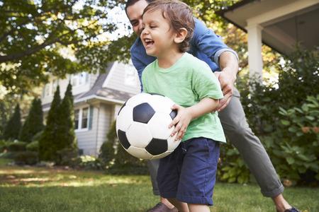 Pai jogando futebol no jardim com filho Foto de archivo