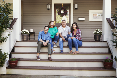 Parents With Adult Offspring Sitting On Steps in Front Of House Standard-Bild