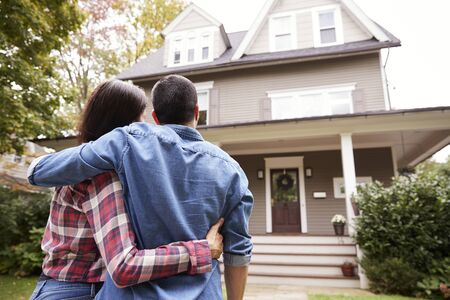 Rear View Of Loving Couple Looking At House Stock Photo