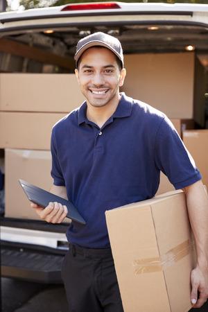 Portrait Of Courier With Digital Tablet Delivering Package Banque d'images