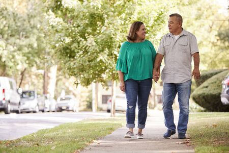 Senior Couple Walking Along Suburban Street Holding Hands Foto de archivo