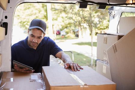 Mensajero con tableta digital comprobación de paquetes en la furgoneta Foto de archivo - 94160076
