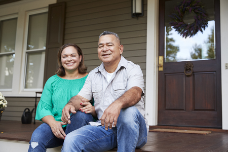 Portrait Of Smiling Senior Couple Sitting In Front Of Their Home Standard-Bild
