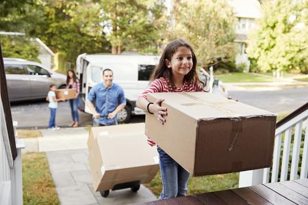日に移動する家族にバンから箱をアンロードするのを助ける子供たち