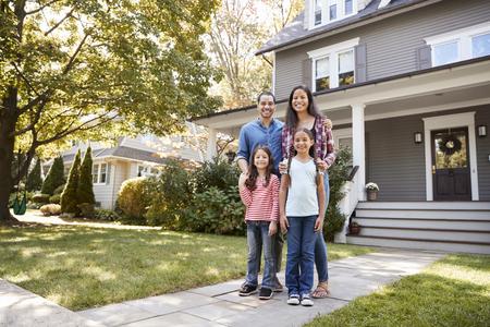 Retrato de familia sonriente parado frente a su casa