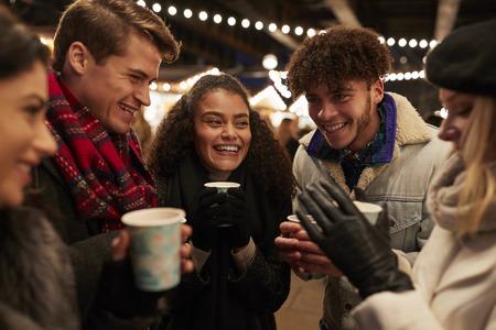 Gruppe Freunde , die Glühwein am Weihnachtsmarkt trinken