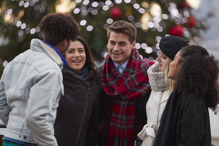 Young Friends On Walk Standing By Christmas Tree