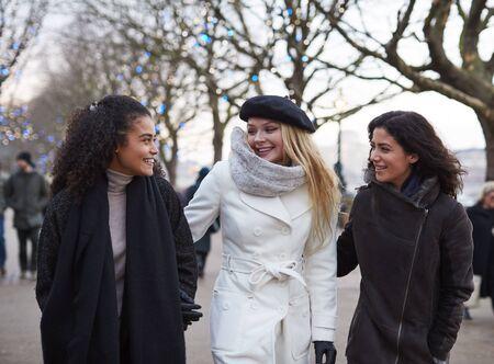 Female Friends Walk Along South Bank On Winter Visit To London Reklamní fotografie