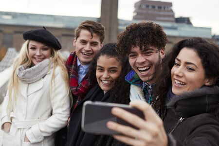Group Of Young Friends Taking Selfie On Winter Visit To London