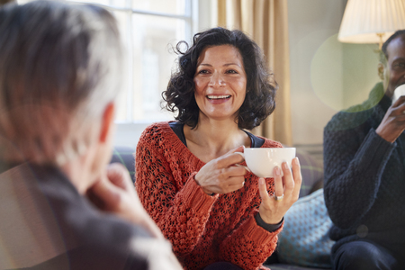Middle Aged Woman Meeting Friends Around Table In Coffee Shop Stock fotó
