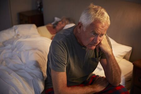 Worried Senior Man In Bed At Night Suffering With Insomnia Foto de archivo