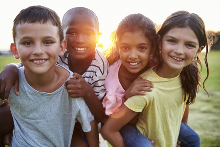 Portrait of smiling young friends piggybacking outdoors Stock Photo
