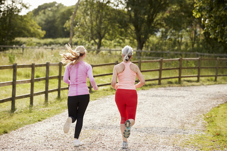 Young And Senior Women Enjoying Run Through Countryside Together