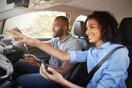 Happy couple in car on a road trip navigate with smartphone
