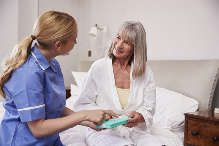 Nurse Helping Senior Woman To Organize Medication On Home Visit