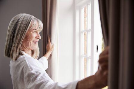 senior femme ouvrant rideaux de la chambre et en regardant par la fenêtre Banque d'images