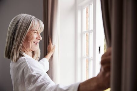 Senior Woman Opening Bedroom Curtains And Looking Out Of Window Archivio Fotografico