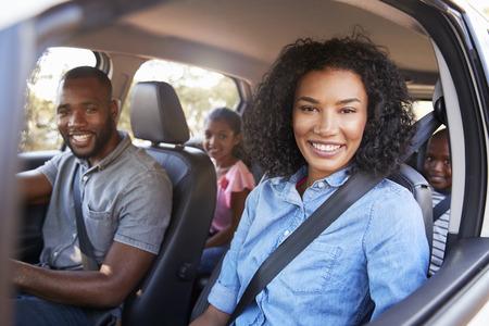 Młoda czarna rodzina w samochodzie na wycieczce drogowej uśmiecha się do kamery