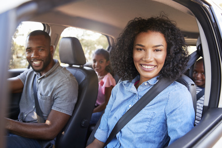 Young black family in a car on a road trip smiling to camera Imagens - 96250415