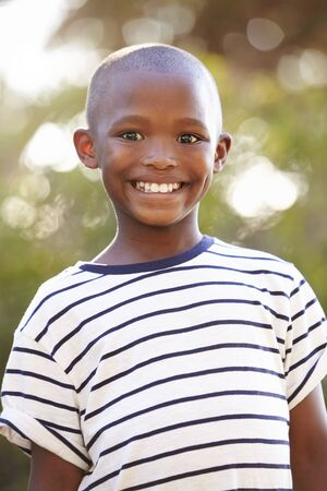 Smiling young black boy looking away from camera outdoors Stock fotó