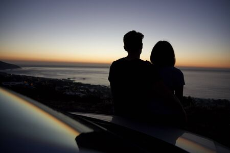 Couple relaxing together by the sea at sunset, silhouette