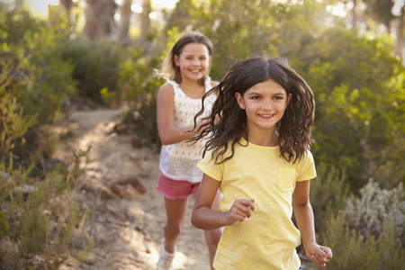 Two happy smiling girls running after each other in a forest